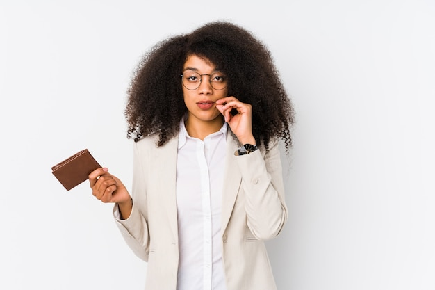 Young afro business woman holding a credit car isolated young afro business woman holding a credit carwith fingers on lips keeping a secret.