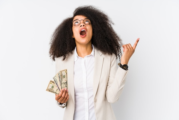 Young afro business woman holding a credit car pointing upside with opened mouth.