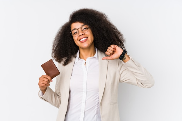 Young afro business woman holding a credit card feels proud and self confident