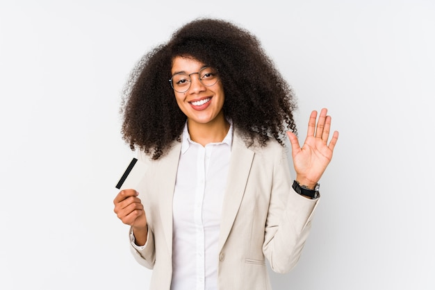 Young afro business woman holding a credit card and showing number five with fingers