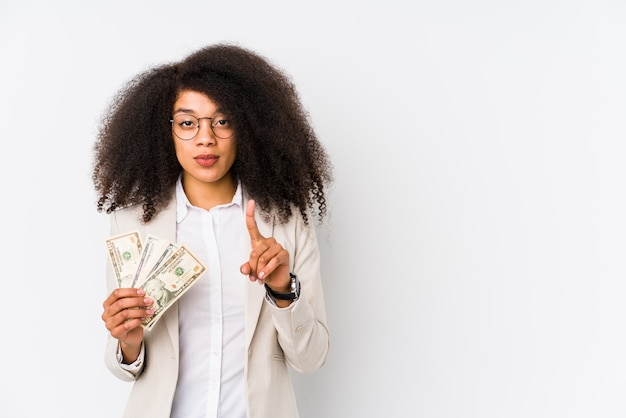 Young afro business woman holding a credit card showing number one with finger