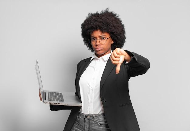 若いアフロの実業家は、真剣な表情で親指を下に向けて、十字架、怒り、イライラ、失望、または不満を感じています。ビジネスコンセプト