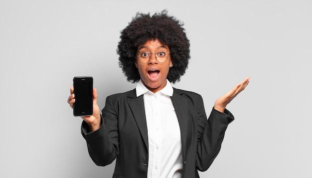 Молодая афро-деловая женщина чувствует себя счастливой, взволнованной, удивленной или шокированной, улыбается и удивляется чему-то невероятному.