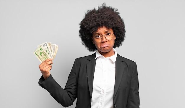 若いアフロの実業家は、不幸な表情で悲しみと泣き言を感じ、否定的で欲求不満の態度で泣いています。ビジネスコンセプト