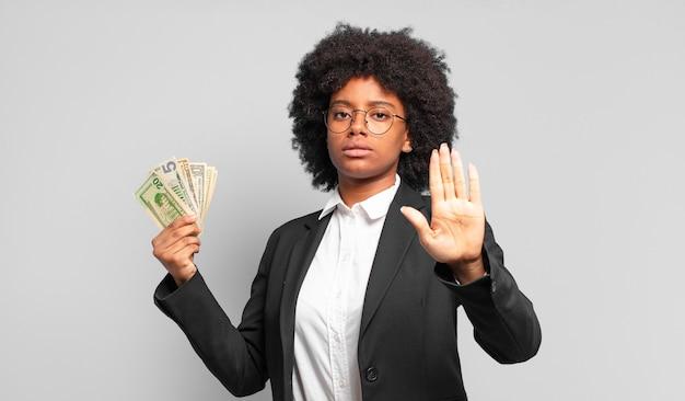真面目で、厳しく、不機嫌で、怒っているように見える若いアフロの実業家は、開いた手のひらが停止ジェスチャーをしていることを示しています。ビジネスコンセプト