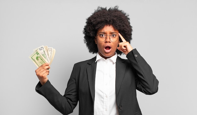 Young afro businesswoman looking surprised, open-mouthed, shocked, realizing a new thought, idea or concept. business concept