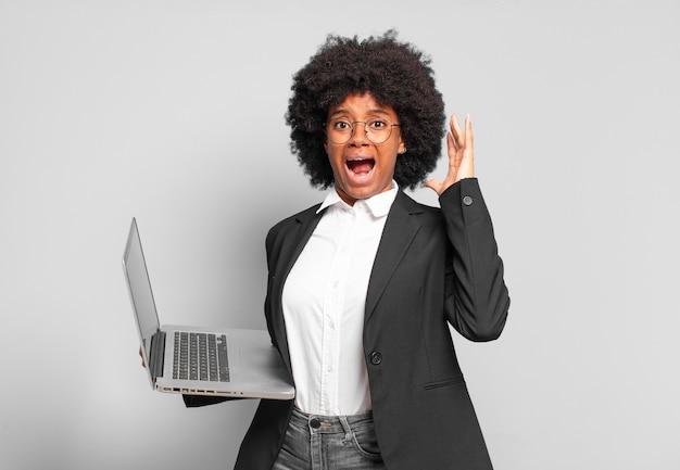 空中で手を上げて叫び、激怒し、欲求不満を感じ、ストレスを感じ、動揺している若いアフロ実業家。ビジネスコンセプト