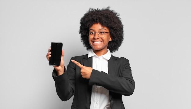 若いアフロの実業家は元気に笑って、幸せを感じて、横と上を指して、コピースペースにオブジェクトを表示します。ビジネスコンセプト
