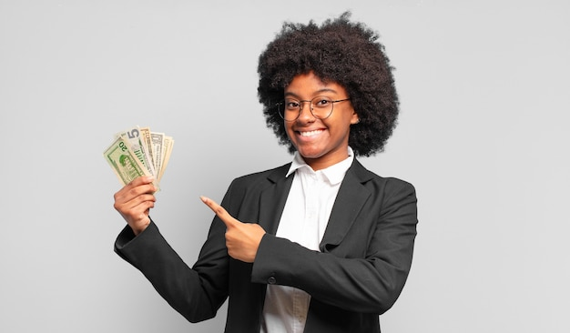 Young afro businesswoman smiling cheerfully, feeling happy and pointing to the side and upwards, showing object in copy space