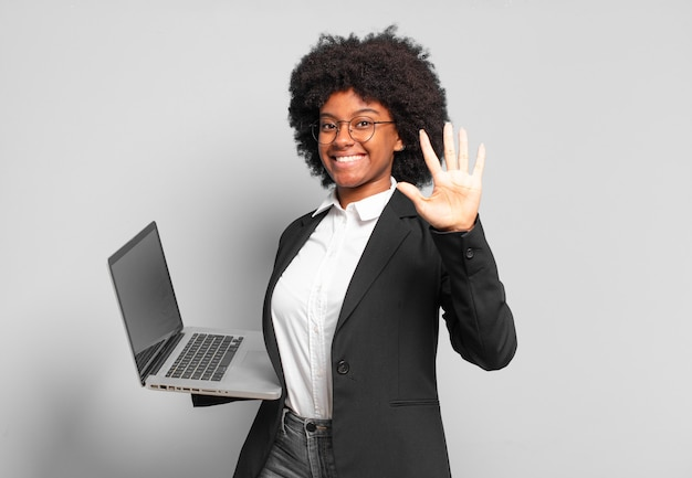 Young afro businesswoman smiling and looking friendly, showing number five or fifth with hand forward, counting down. business concept