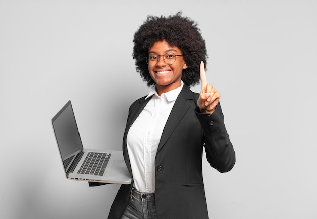 Young afro businesswoman smiling and looking friendly, showing number one or first with hand forward, counting down. business concept