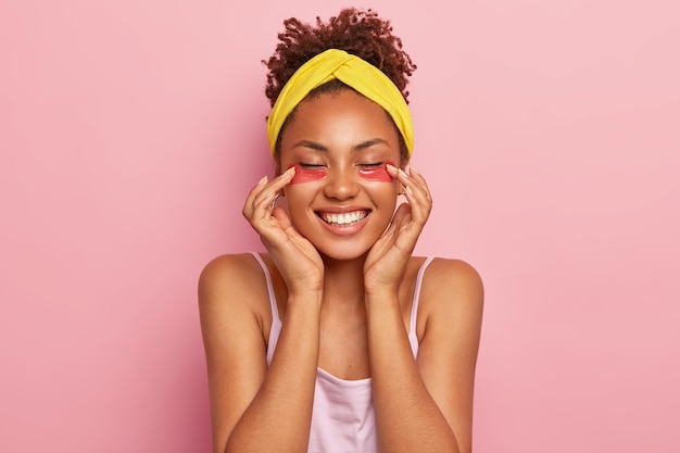 Young afro female model applies collagen pads under eyes, enjoys moisturizing treatment, smiles broadly, shows white teeth has fresh healthy skin wears yellow headband