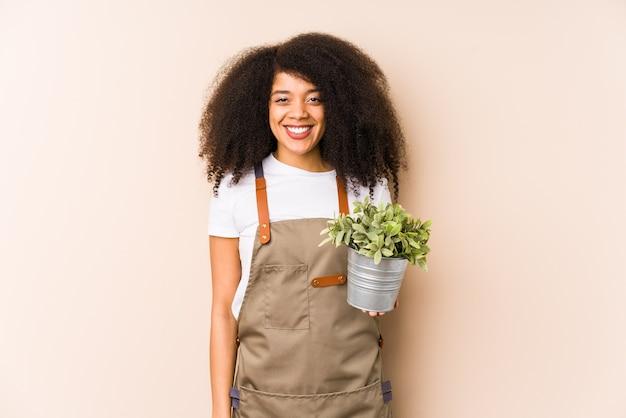 分離された植物を保持している若いアフロ庭師女性幸せ、笑顔、陽気です。