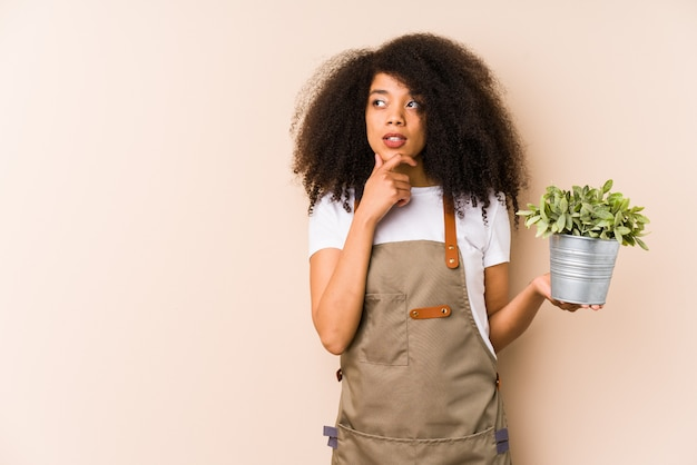 Young afro gardener woman holding a plant isolatedlooking sideways with doubtful and skeptical expression.