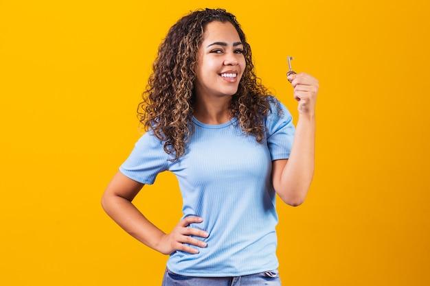 Молодая афро девушка держит ключ от дома.