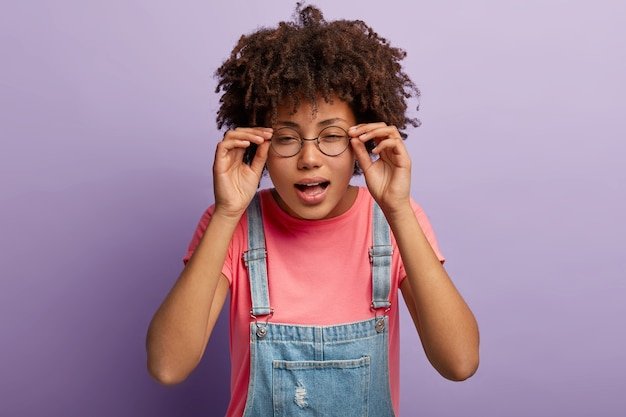 Young afro girl keeps hands on frame of glasses, tries to concentrate