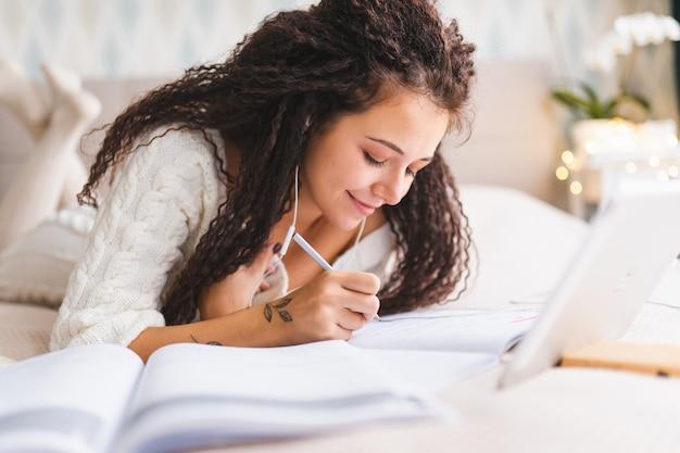 家庭服を着た若いアフロヘアミックスレースの女性がベッドに横になって宿題をします。遠隔教育または仕事の概念。