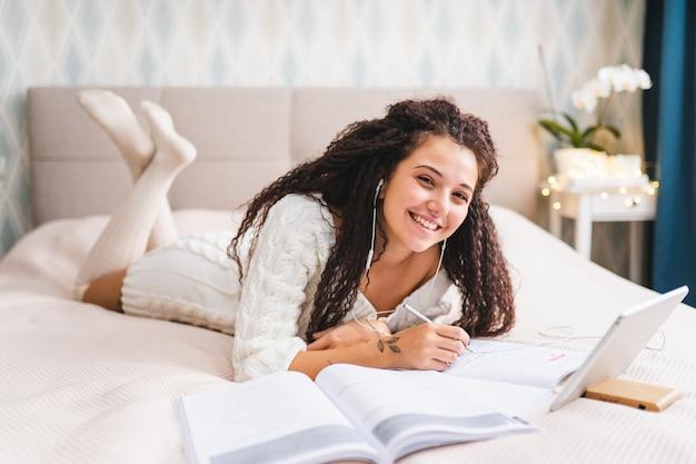 家庭服を着た若いアフロヘアミックスレースの女性がベッドに横になり、タブレットでオンラインレッスンを行っています。遠隔教育または仕事の概念、