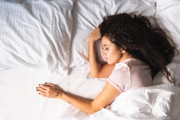 Молодая афро-волосатая расстроенная женщина одна в постели с пустым местом рядом с ней. развод, потеря концепции любви, вид сверху.