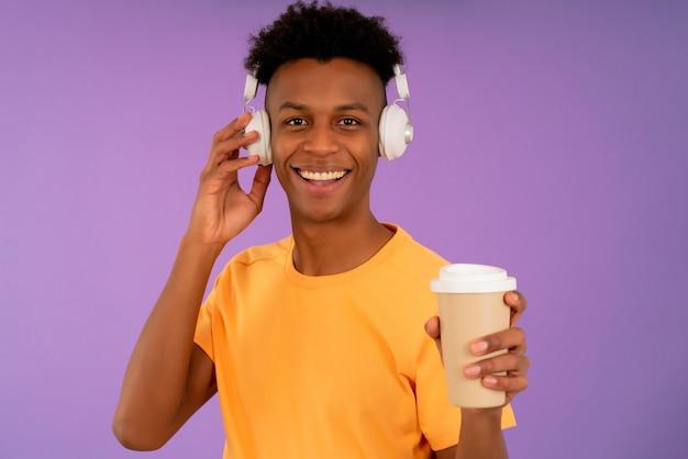 孤立した背景の上にテイクアウトコーヒーのカップを保持しながら、ヘッドフォンで音楽を聴いて楽しんでいる若いアフロ男。