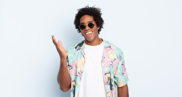 Молодой афро-мужчина чувствует себя счастливым, удивленным и веселым, улыбается с позитивным настроем, реализует решение или идею