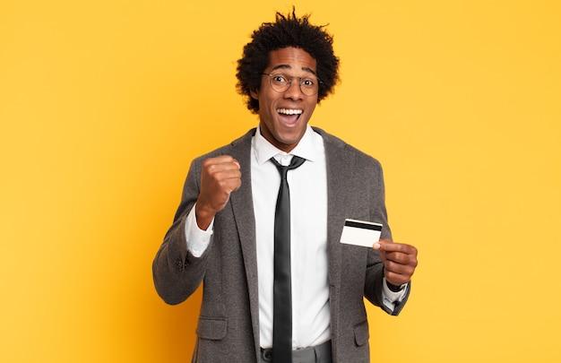 젊은 아프리카 남자는 충격을 받고 흥분하고 행복하며 웃고 성공을 축하하며 와우라고 말합니다!