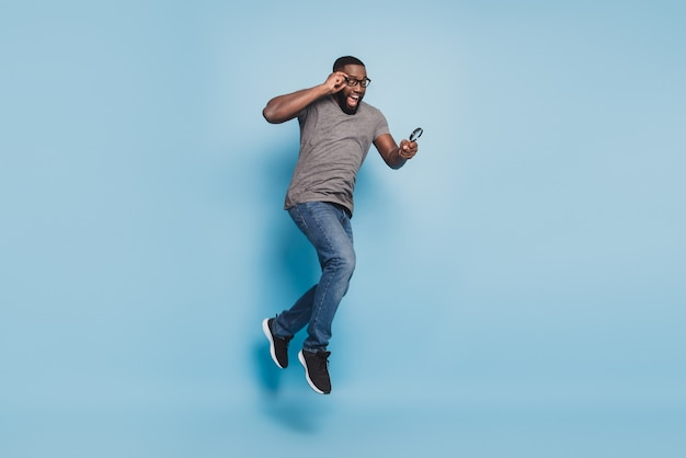 Young afro man jump look magnifying glass isolated over blue background