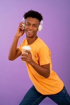 ヘッドフォンで音楽を聴いている若いアフロ男。