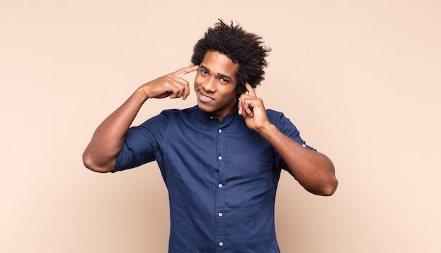 Молодой афро-мужчина выглядит озадаченным и сбитым с толку, нервно прикусывает губу, не зная ответа на проблему