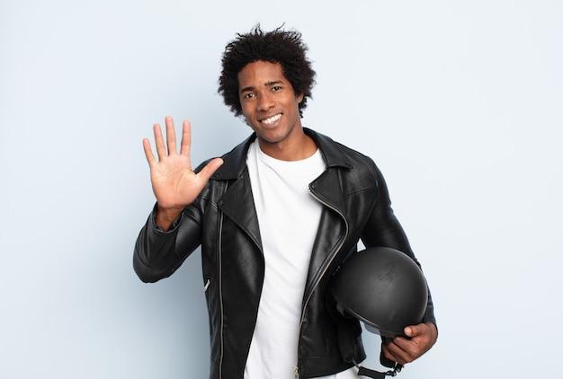 若いアフロマンは笑顔でフレンドリーに見え、手を前に向けて5番または5番を示し、カウントダウンします