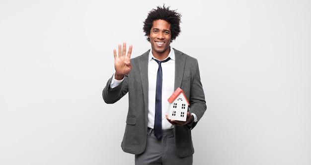 Молодой афро-мужчина улыбается и выглядит дружелюбно, показывает номер четыре или четвертый с рукой вперед, считая