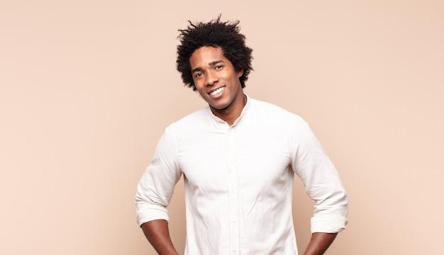 Молодой афро-мужчина весело и небрежно улыбается с позитивным, счастливым, уверенным и расслабленным выражением лица