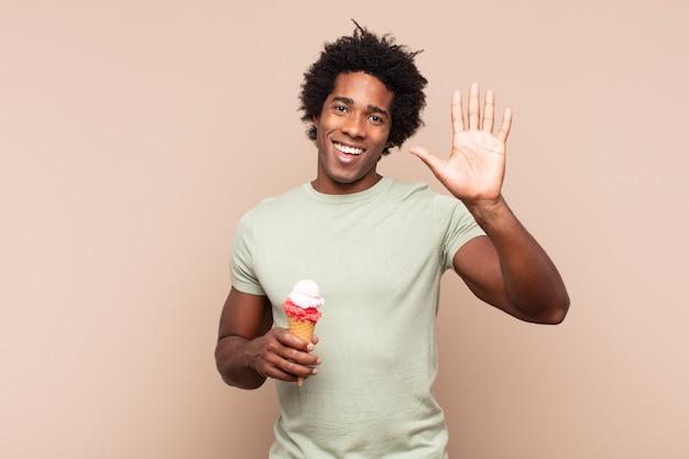 楽しく元気に笑ったり、手を振ったり、歓迎して挨拶したり、さようならを言ったりする若いアフロマン