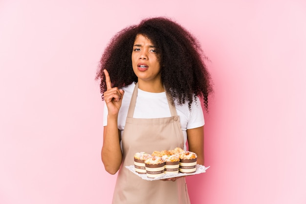 Young afro pastry maker woman holding cupcakes