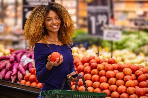 Молодые афро выбирают помидоры на рынке