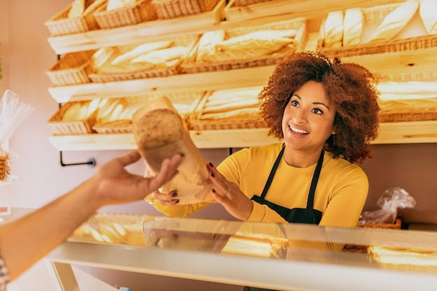Young afro woman baker in a bakery, giving a cereal bread stick to a client, smiling and happy.
