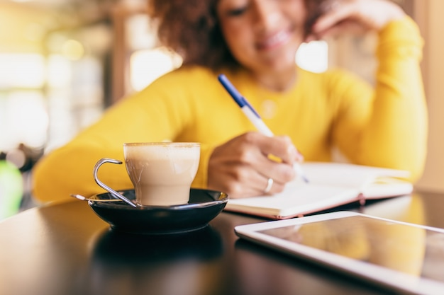 Young afro woman at cafe. she is writing in a notebook, closeup of a coffee.