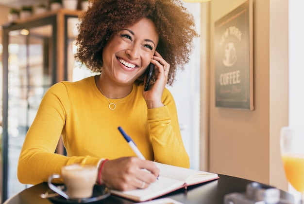 Young afro woman in a coffee shop, smiling and confident, talking on a mobile phone.