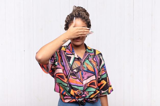 片手で目を覆っている若いアフロ女性は、怖い、不安を感じ、不思議に思ったり、盲目的に驚きを待っている
