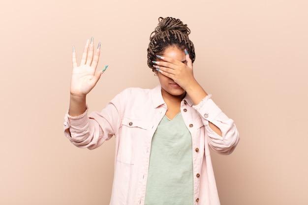 Молодая афро-женщина закрывает лицо рукой и поднимает другую руку вперед, чтобы остановить камеру, отказываясь от фотографий или изображений