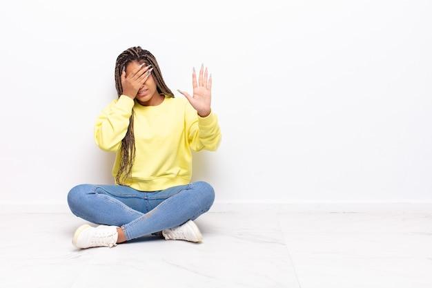 Молодая афро женщина закрыла лицо рукой и подняла другую руку