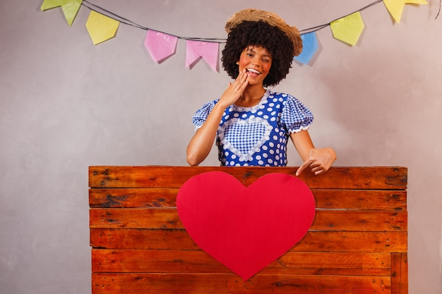 Young afro woman dressed for junina party behind a wooden board with a heart