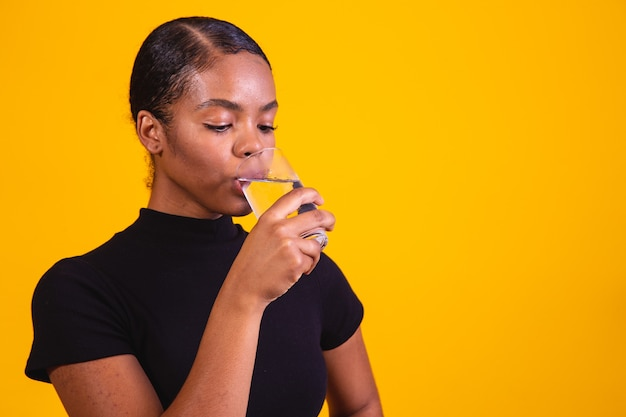 Young afro woman drinking water in yellow background. young girl with glass of water