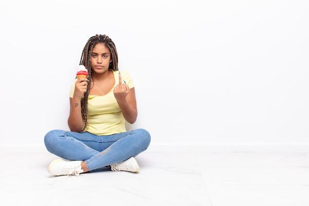 怒り、イライラ、反抗的、攻撃的で、中指をひっくり返し、反撃する若いアフロ女性
