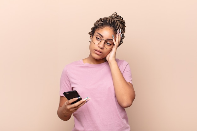 지루하고 지루하고 지루한 작업 후 지루하고 좌절하며 졸린 젊은 아프리카 여성이 손으로 얼굴을 잡고 있습니다. 스마트 폰 개념