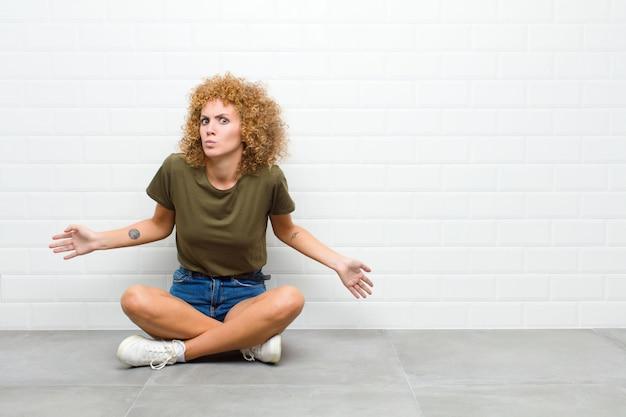 젊은 아프리카 여자 단서와 혼란을 느끼고 전혀 몰라 바닥에 앉아 바보 또는 어리석은 표정으로 의아해합니다.