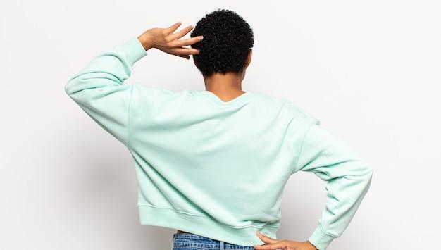 젊은 아프리카 여성이 우둔하고 혼란스러워하는 느낌, 엉덩이에 손, 머리에 다른 손으로 해결책을 생각, 후면보기