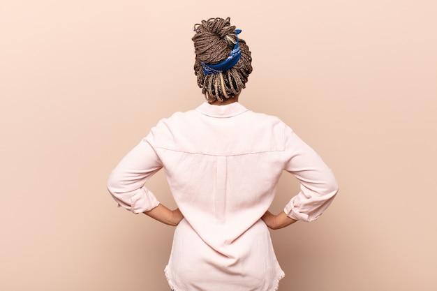 Молодая афро-женщина чувствует себя растерянной или полной или сомневается и задается вопросом, с руками на бедрах, вид сзади