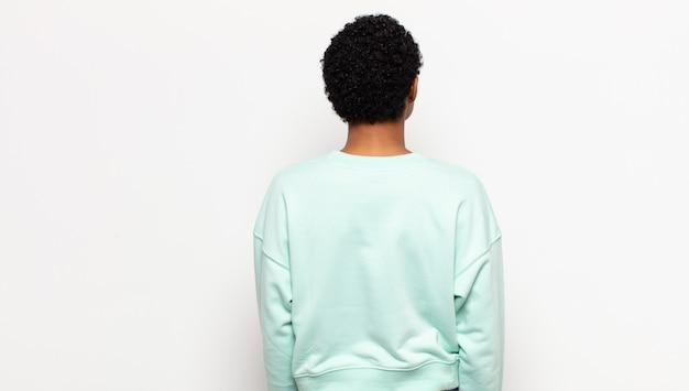 Молодая афро-женщина, чувствуя себя растерянной или наполненной, или сомнениями и вопросами, недоумевая, с руками на бедрах