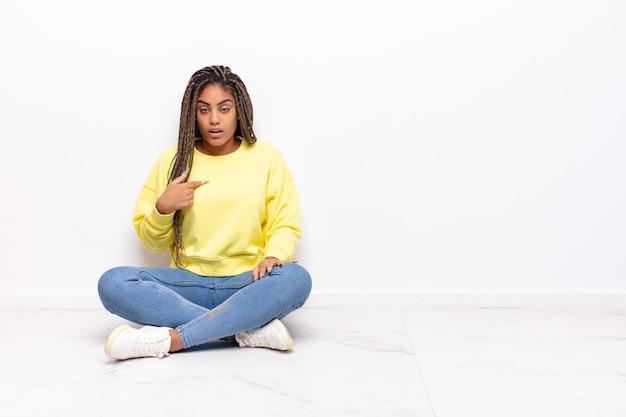 Молодая афро-женщина чувствует себя смущенной, озадаченной и неуверенной, указывая на себя, удивляясь и спрашивая, кто, я?